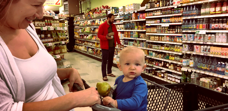 child in shopping cart holding a pear